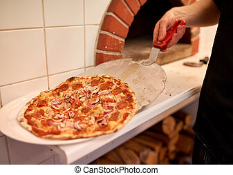 chef placing pizza from peel to plate at pizzeria - food,...