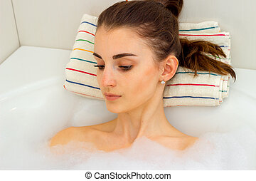 Portrait of a beautiful girl with dark hair that is in the water in the bathroom and lowered her eyes down