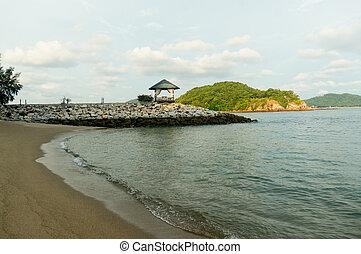 Long shot of a beach and hut - Long shot of a sandy beach...