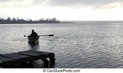 fisherman swims on an old boat to the stony bank at dusk