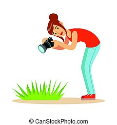 Beatuful woman taking picture of green grass with her camera.