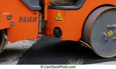 Steamroller is spreading, flatting hot asphalt. - Hot...