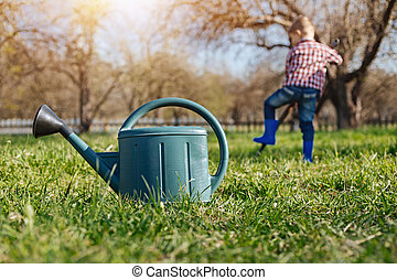 Scaled up shot of watering can on grass - Looking after...