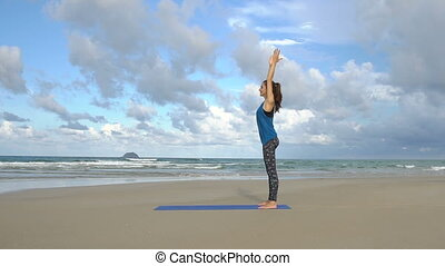The girl is making yoga pose on beach in Vietnam. Sea or ocean happy woman relaxation. Exercises calmness and harmony.