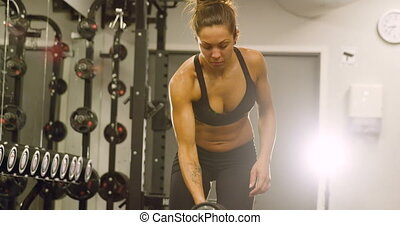 Focused fit woman training lats and lifting weights in...