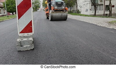 Steamroller is spreading hot asphalt - Steamroller is...