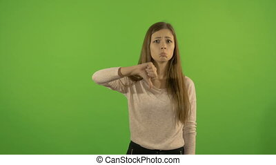 Beautiful young model on a background of a green screen. Shows his thumb down.