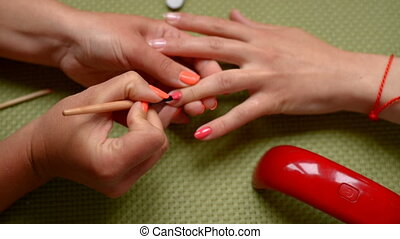 Manicure red nail polish. - Manicure applying red nail...