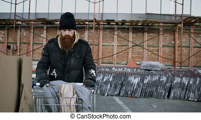 Dolly shot of bearded homeless man walking down the street with shooping card at cold autumn day