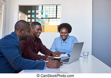 Smiling young African businesspeople working on a laptop together