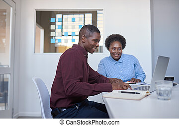 African businesspeople working on a laptop in a modern office