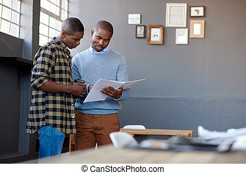 African office coworkers discussing paperwork together in a modern office