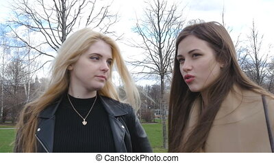 Beautiful blonde and brunette talking on the street. Good...