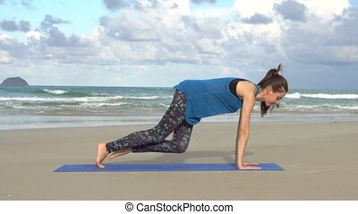 Young woman training on the beach in front of sea. Morning gymnastic. Plank exercise. Healthy active lifestyle concept.