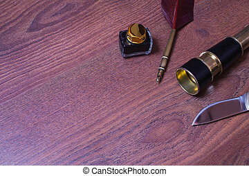 hunting knife, fountain pen and ink, spyglass on wooden background, copyspace
