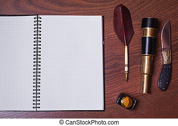 a sheet of paper from a notebook, a hunting knife, fountain pen and ink, spyglass on wooden background, copyspace