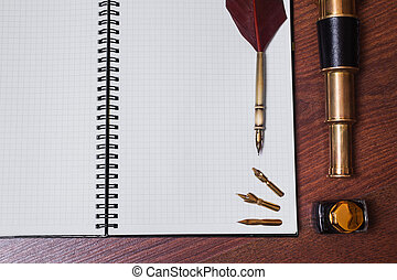 a sheet of paper from a notebook, fountain pen and ink, spyglass on wooden background, copyspace