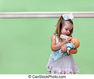 Childhood nurturing - Little girl pretends to be a mother,...