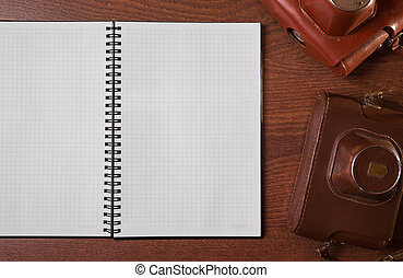 a sheet of paper from a notebook, case for the camera on wooden background, copyspace
