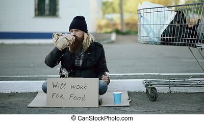 Bearded young homeless man with cardboard sitting near shopping cart and drink alcohol at cold day