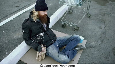Homeless young man in dirty clothes drink alcohol sitting...