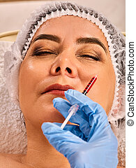 Dermal fillers lips of woman in spa salon with beautician.