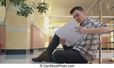 man sitting on floor, looking documents with drawings in office.