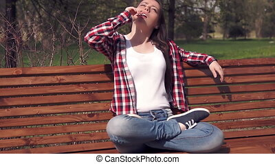 Teenage girl sitting on bench and licking candy
