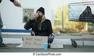 Young man helps to homeless person and giving him some food...