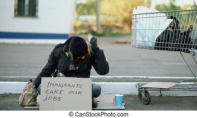 Angry upset young homeless man with cardboard sitting near...