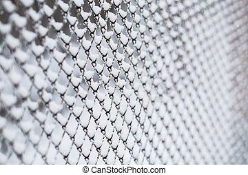 Lattice fence covered with snow. Winter time. Heavy snowfall.