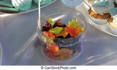 A lot of a gummy candy in a transparent box made of plastic or a glass on a white tablecloth. Slow motion shot.
