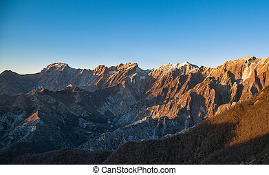 Apuane alpi snowy mountains and marble quarry at sunset in...