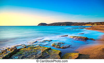 Baratti beach bay, headland hill, rocks and sea on sunset....