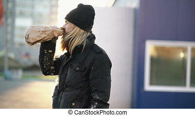 Drunk homeless man with drink alcohol from paper bag while...
