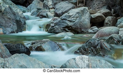 Time lapse of mountain river. Fast water flow, stones, waterfall