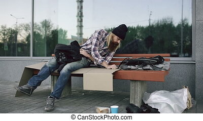 Young Homeless man trying to sleep under jacket on bench at the sidewalk