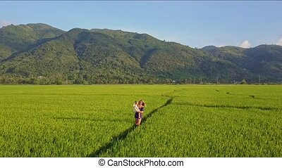Aerial View Woman Carries Girl among Fields against Mountains