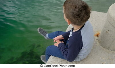 Little boy dangles his legs sitting of the side a pier. Dark...