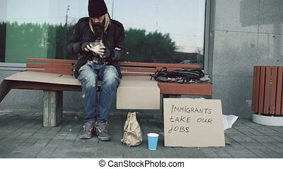 Homeless and jobless european man with cardboard sign eat...