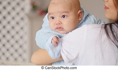 Cute Asian baby in mother arms