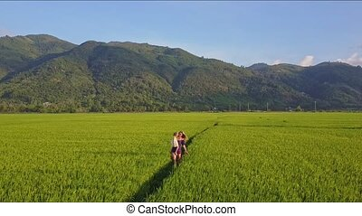 Woman Carrying Girl Approaches Drone Camera among Fields -...