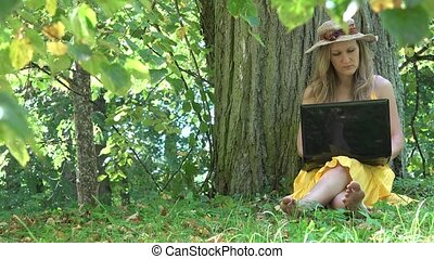 student woman work with laptop computer in nature green park. 4K
