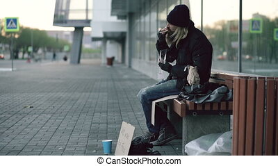 Homeless young man eating sandwich and drinking alcohol from...