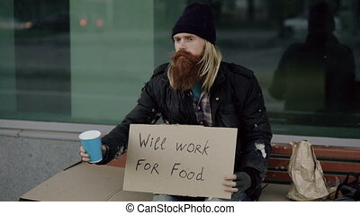 Homeless young man beg for money shaking cup to pay...