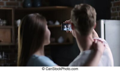 Positive couple taking selfie together at home - Back view...