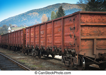Wagons of a freight train on the railway in the mountains.
