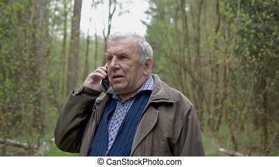 A man of age, walking in the park and talking on his mobile phone. In evening time.