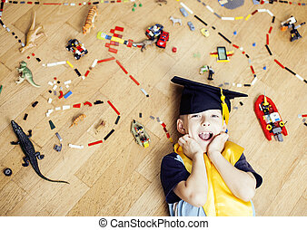 little cute preschooler boy among toys at home education in graduate hat smiling posing emotional, lifestyle people concept