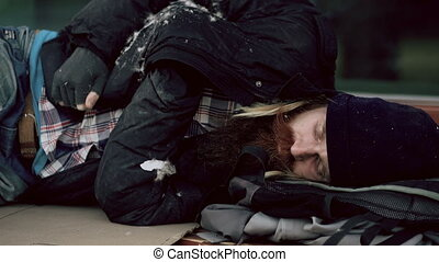 Young homeless drunk man trying to sleep on cardboard on bench at the sidewalk